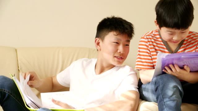 vídeos de stock e filmes b-roll de two chinese brothers doing homework! - pasta