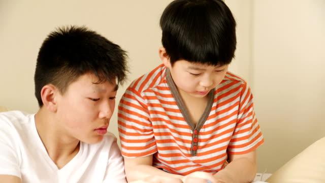 vidéos et rushes de deux frères chinois à faire leurs devoirs! - gomme