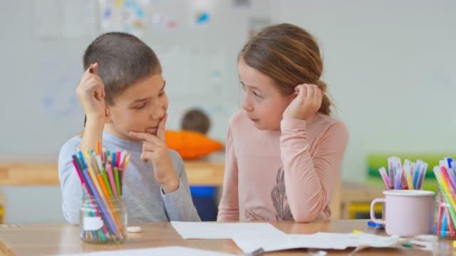 2人の同級生、男の子と女の子、動物の描き方を話し合う - 学校備品点の映像素材/bロール