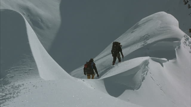 Two climbers move slowly as they make their way across a snowy ridge.