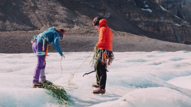 two climbers (male and female) prepare climbing equipment on the athabasca glacier before ice climbing out of a mill well crevasse in 4k - climbing equipment stock videos & royalty-free footage