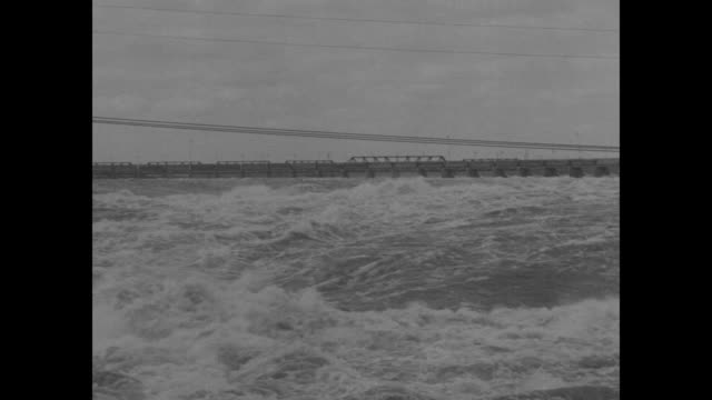 two close shots of floodwater rushing down river / wide stretch of rushing floodwater, bridge in background, pan across to building next to water /... - depth marker stock videos & royalty-free footage