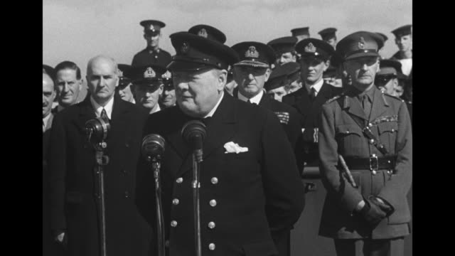 two close ups of british prime minister churchill wearing military cap speaking into microphones / wider shot of churchill speaking british military... - president stock videos & royalty-free footage