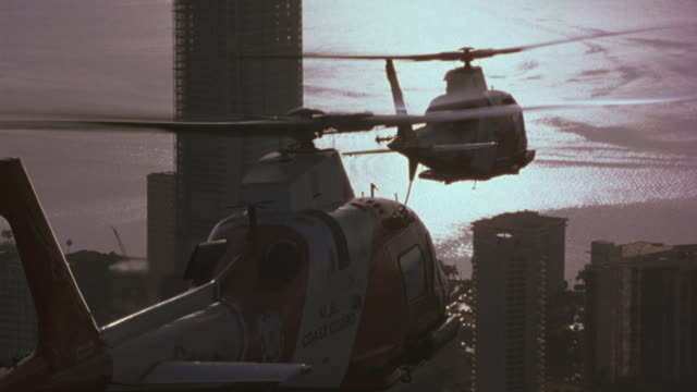 two coast guard helicopters fly above high-rise buildings in a downtown coastal area. - helicopter stock videos & royalty-free footage