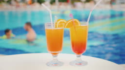 Two cocktails with straws on the background of the pool. The pool blurred contours father teaches his daughter to swim. Holiday with children in a luxury resort concept