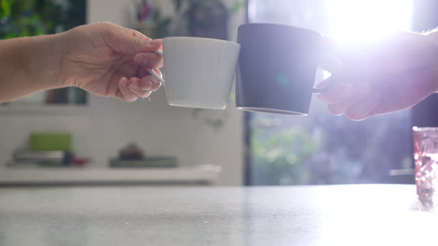 two coffee cups clinking together in kitchen - hot drink stock videos & royalty-free footage