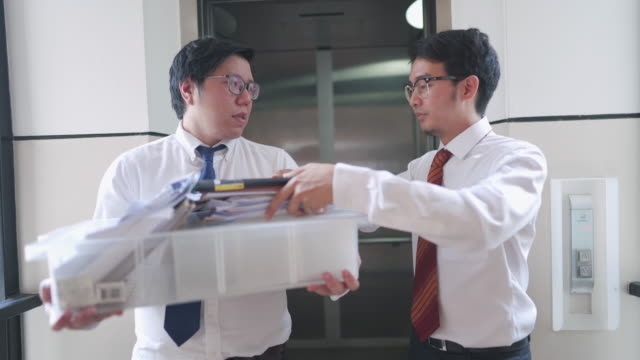 two colleague coming out of elevator with office supplies, moving office concept - moving office stock videos & royalty-free footage