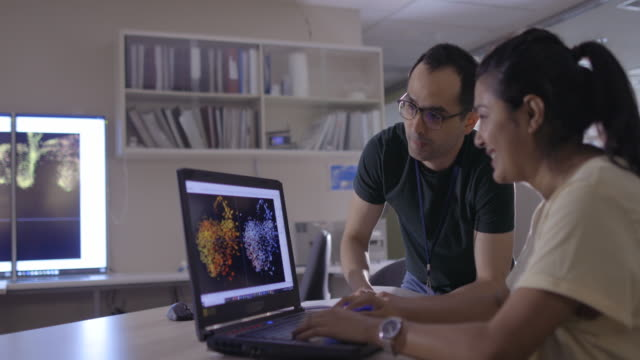 vídeos de stock, filmes e b-roll de dois colegas discutem apresentação - biologia