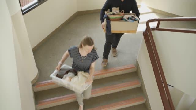 vídeos y material grabado en eventos de stock de dos colegas moviendo sus cosas por escaleras, oficina móvil o lugar de trabajo - embalaje