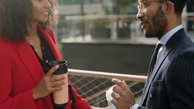 ビジネスビルの前でコーヒーブレイクの2人の同僚 - ウォーターボトル点の映像素材/bロール