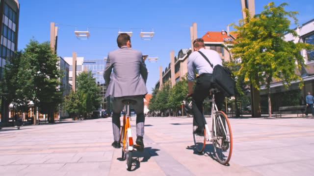 市内で自転車に乗って slo mo 2 人の同僚 - 後ろ姿点の映像素材/bロール