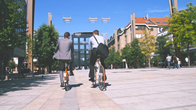 slo mo two colleagues riding their bicycles to work - courtyard stock videos & royalty-free footage