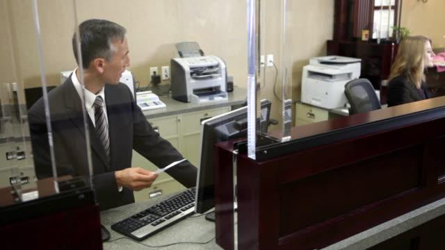 two colleagues working in bank - 窓口点の映像素材/bロール