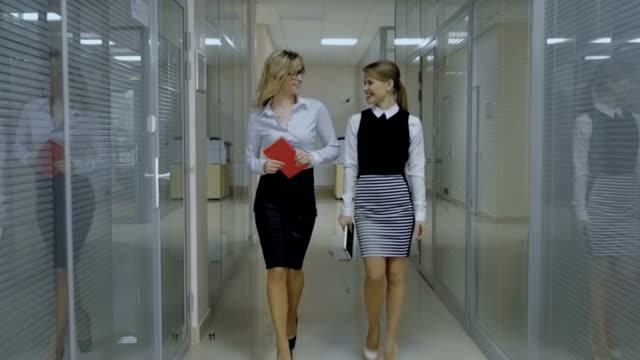 vídeos de stock, filmes e b-roll de dois colegas fala uma caminhada ao longo do corredor - secretária