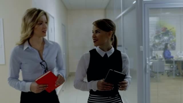 Två kollegor föredrag går längs korridoren