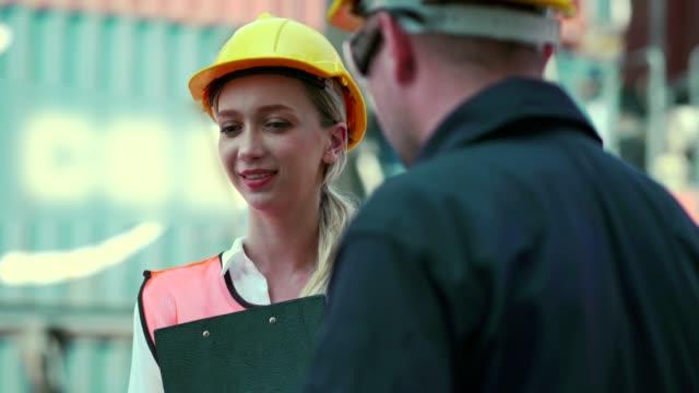 vidéos et rushes de discussion de travail de travailleur de docks commerciaux - débardeur