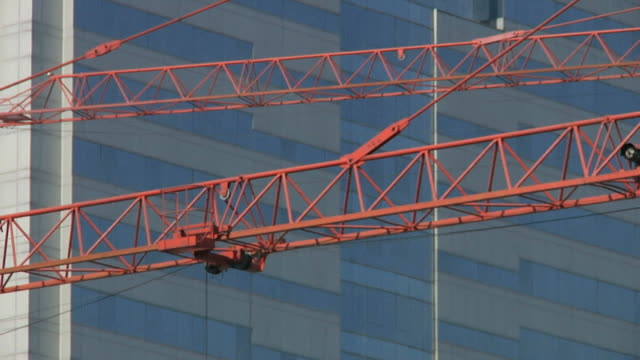 stockvideo's en b-roll-footage met cu two construction cranes moving in front of building / ningbo, zhejiang, china - ningbo