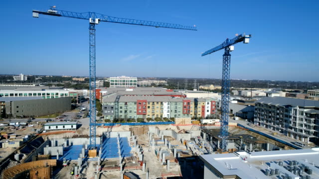 two construction cranes with buildings blue sky and blue cranes building a new development - appartamento video stock e b–roll