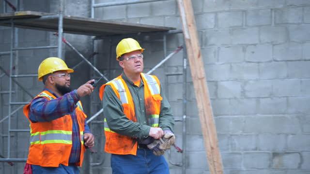 vidéos et rushes de deux ouvriers de la construction sur le chantier marchent, parlent - lunettes de protection