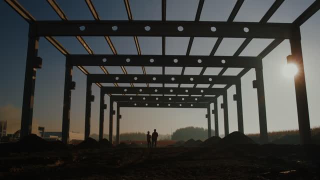 vidéos et rushes de slo mo deux ouvriers de la construction sur le chantier - amélioration