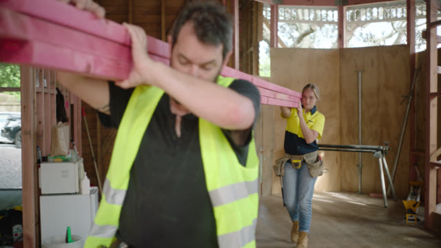 vidéos et rushes de two construction workers carry timber through construction site - carrying