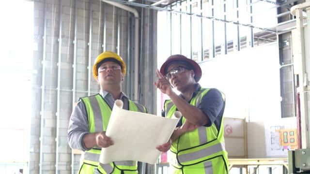 zwei bauarbeiter schauen sich grundriss an - grundriss stock-videos und b-roll-filmmaterial