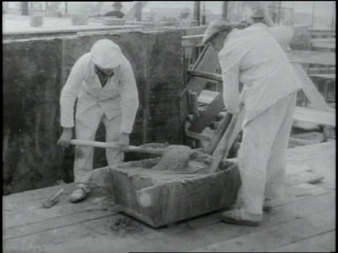 Two construction workers mix cement while another stacks bricks to build the Berlin Wall
