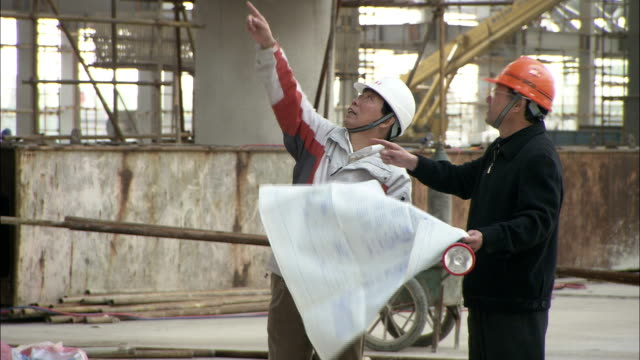 two construction workers point around a construction site while holding blueprints. - qualitätsprüfer stock-videos und b-roll-filmmaterial