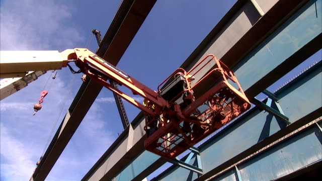 two construction workers ride a basket crane next to steel beams. - construction frame stock videos & royalty-free footage