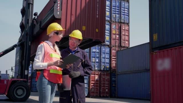 vidéos et rushes de deux employés de terminal à conteneurs vérifiant le chargement des conteneurs de fret - débardeur