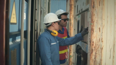 two container terminal employees talking and checking container cargo - examining stock videos & royalty-free footage