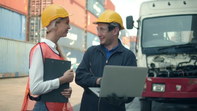 zwei mitarbeiter des containerterminals im gespräch und mit laptop - dockarbeiter stock-videos und b-roll-filmmaterial