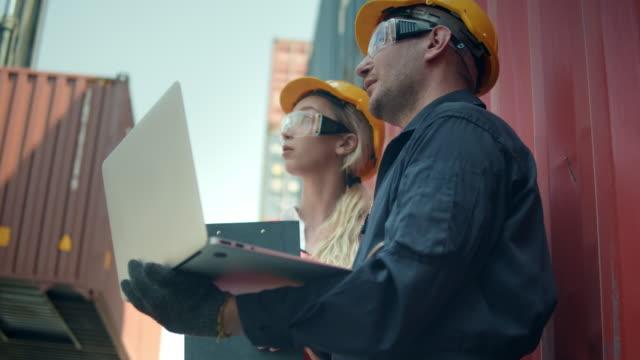 zwei mitarbeiter des containerterminals im gespräch und mit laptop - container stock-videos und b-roll-filmmaterial