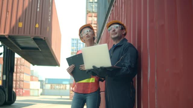 vidéos et rushes de deux employés de terminal de conteneurs parlant et utilisant l'ordinateur portatif - débardeur