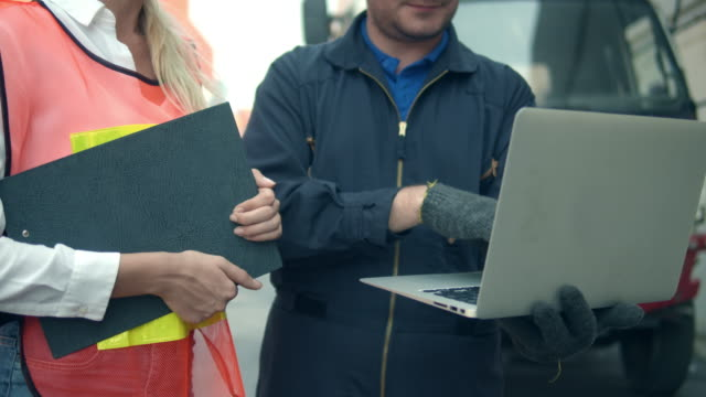 vidéos et rushes de deux employés de terminal de récipient parlant et utilisant l'ordinateur portatif, le gros-plan - débardeur