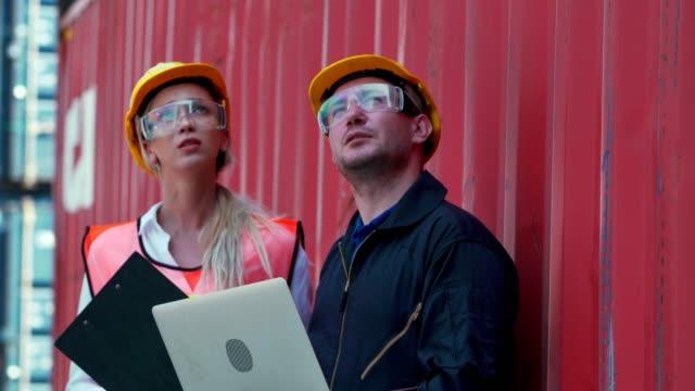 vidéos et rushes de deux employés de terminal de conteneur utilisant l'ordinateur port dans le port d'expédition, brainstorming - débardeur