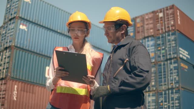 due dipendenti del terminal container che lavorano e parlano di fronte a pile di container colorati nel porto di spedizione - container video stock e b–roll