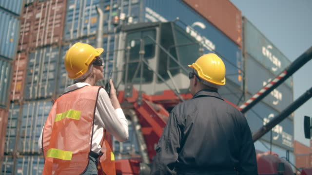 two container terminal employees working and talking in front of colorful cargo container stacks in shipping port - docks stock videos & royalty-free footage