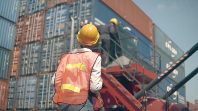 zwei mitarbeiter des containerterminals arbeiten vor bunten frachtcontainerstapeln im schiffshafen - dockarbeiter stock-videos und b-roll-filmmaterial