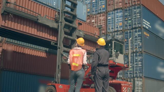 zwei mitarbeiter des containerterminals arbeiten vor bunten frachtcontainerstapeln im schiffshafen - box container stock-videos und b-roll-filmmaterial
