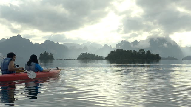 two couple Canoeing on Cheow Lan lake, Thailand in the morning.