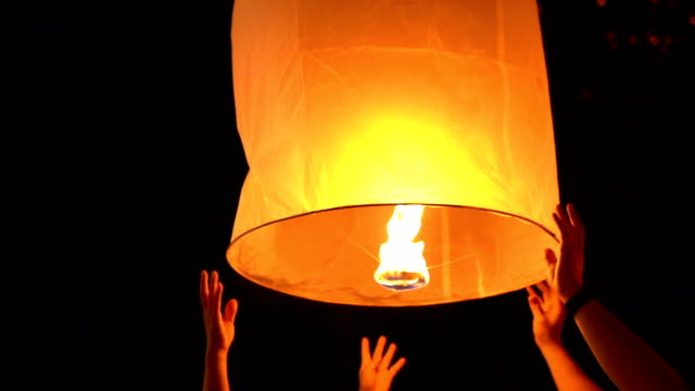 two couple hands release floating sky lantern to the sky - sky lantern stock videos & royalty-free footage