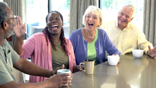 2組のカップルが話し合い、コーヒーを飲む - カップ点の映像素材/bロール