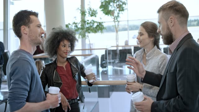 two couples drinking coffee and talking while waiting at the airport - airport terminal stock videos & royalty-free footage
