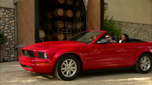 ws two couples driving up to winery entrance in red convertible / paso robles, california, usa - 降り立つ点の映像素材/bロール
