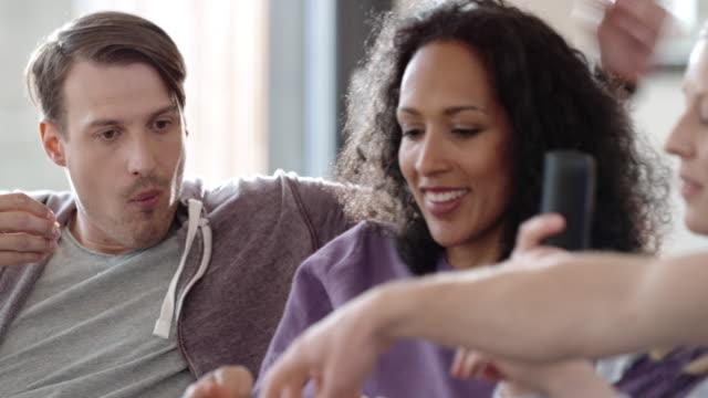 vídeos de stock, filmes e b-roll de dois casais comendo pipoca e assistindo tv - pipoca