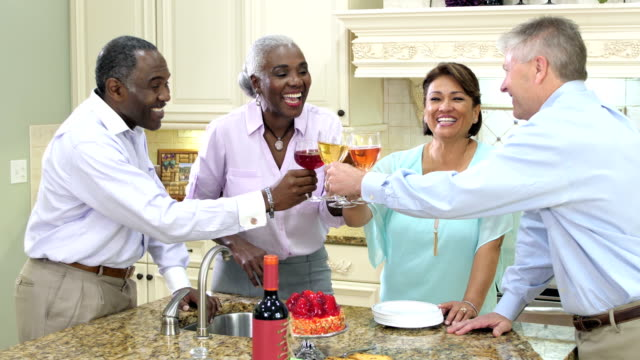 Two couples in kitchen drinking wine, socializing, toast