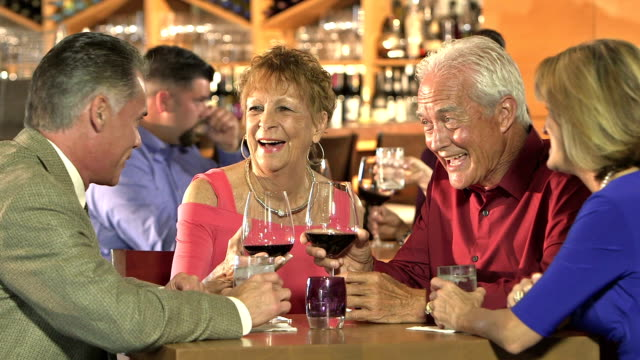 Two couples in restaurant talking and drinking