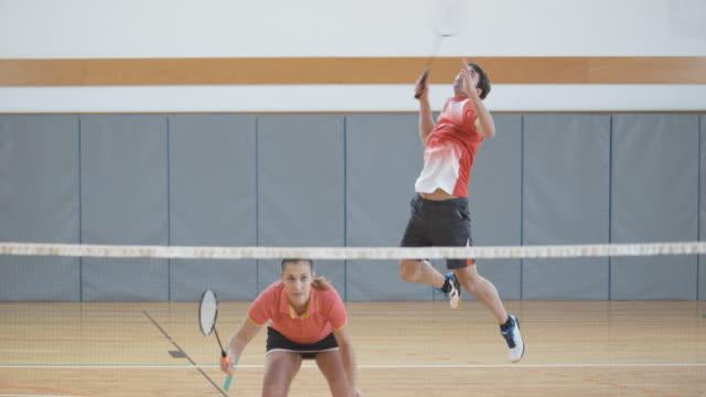 vídeos de stock, filmes e b-roll de dois casais jogando badminton indoor - badmínton esporte
