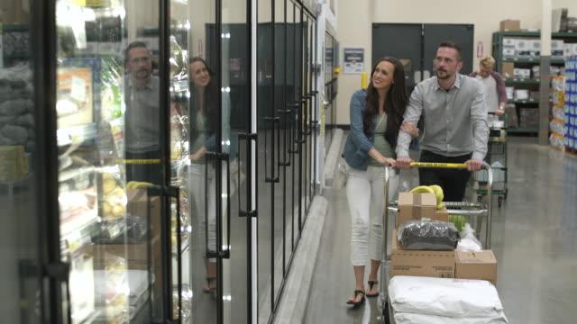 vídeos de stock, filmes e b-roll de two couples shopping in a warehouse supermarket - de braços dados